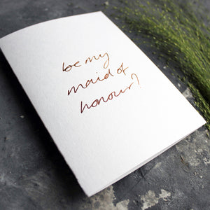 this hand foiled card asks 'be my maid of honour?' on the front in handwriting on white paper