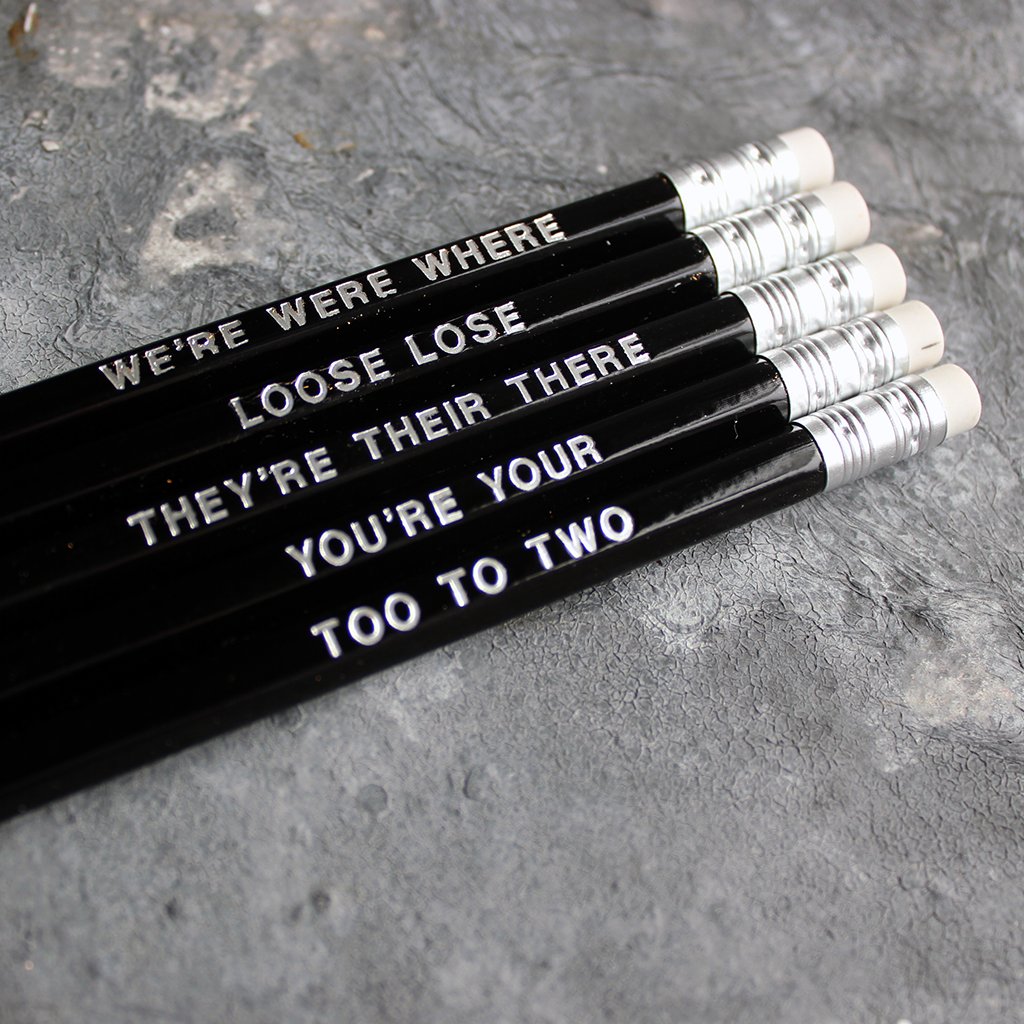 Black HB pencils printed with silver foil phrases and packaged in a grey paper box.