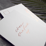 a hand pressed rose gold foil postcard that says Cheer The Fuck Up