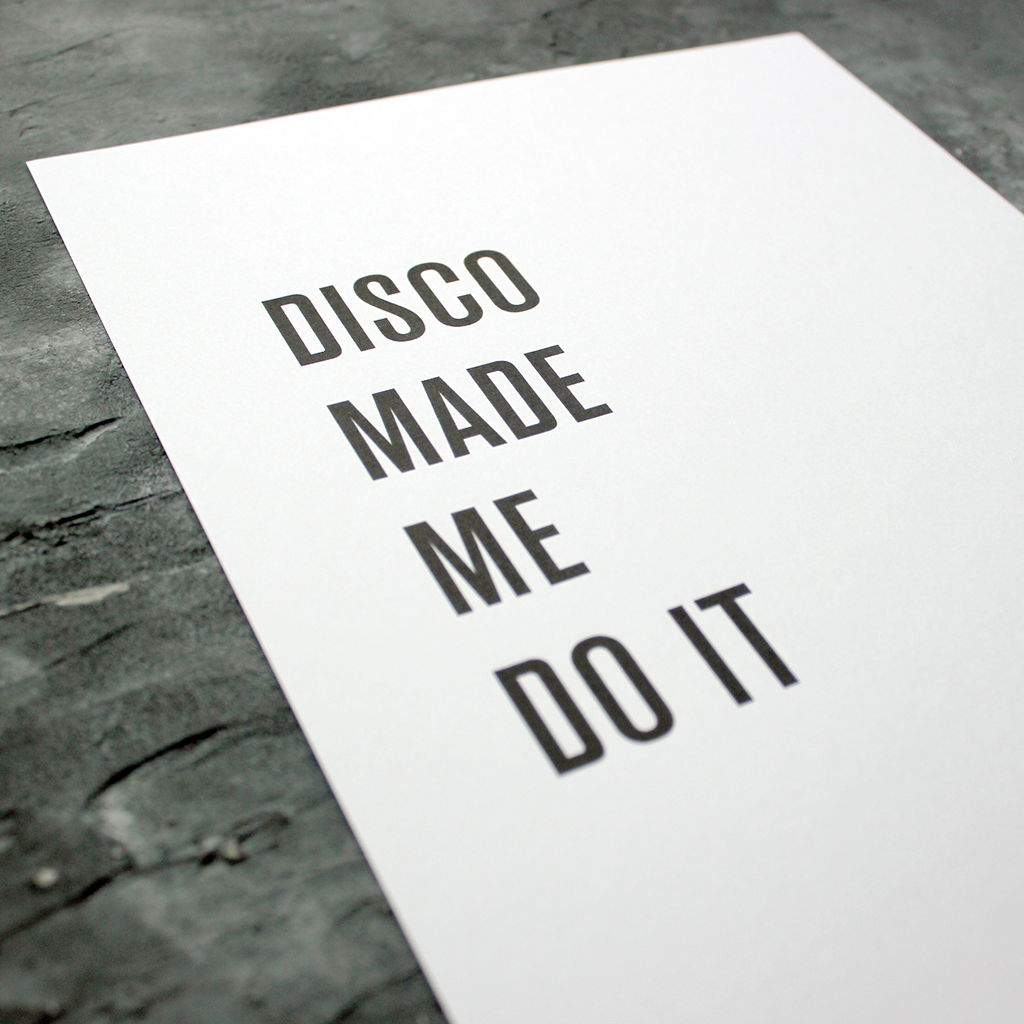 The words 'Disco Made Me Do It' is a black and white typographic design in a frame