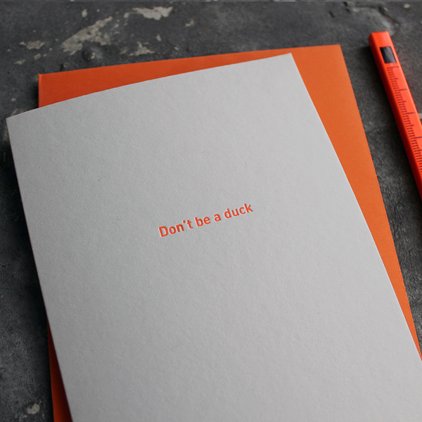 The front of the grey card says Don't Be A Duck and is stamped in neon orange foil