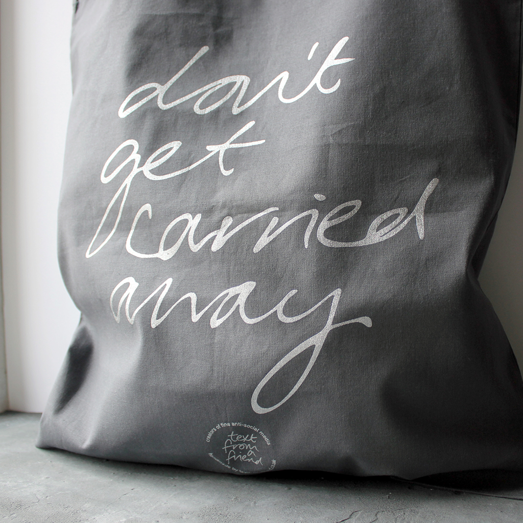 100% cotton grey tote bag hand screen printed in silver metallic ink with a handwritten message that says 'don't get carried away'