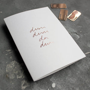 This rose gold hand foiled luxury white card says Dum Dum Da Dum on the front in handwriting from Text From A Friend