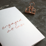 A hand printed engagement card with Rose gold foil on the front says 'Engaged At Last'