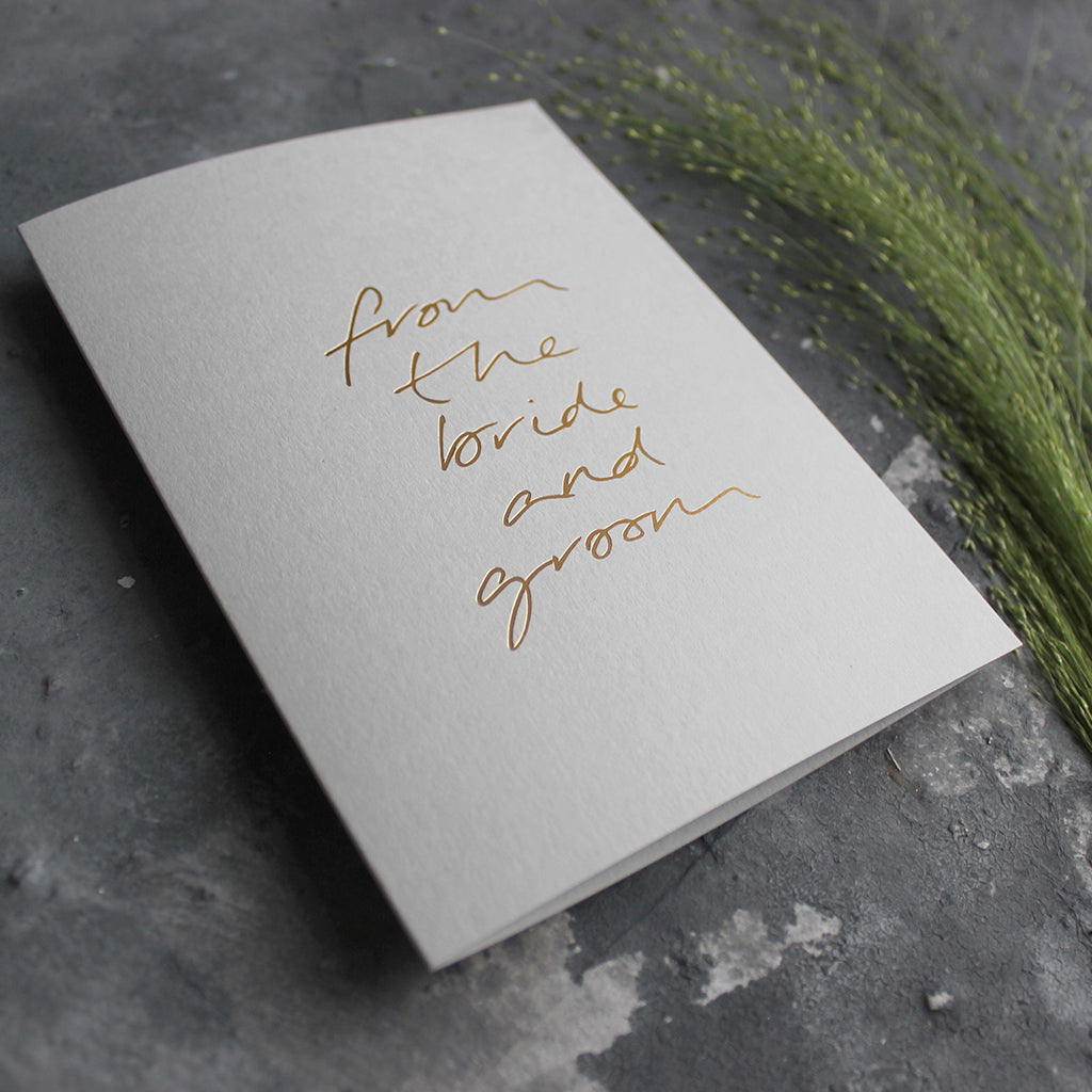 This hand foiled thank you card says 'From The Bride And Groom' on the front on pale grey paper
