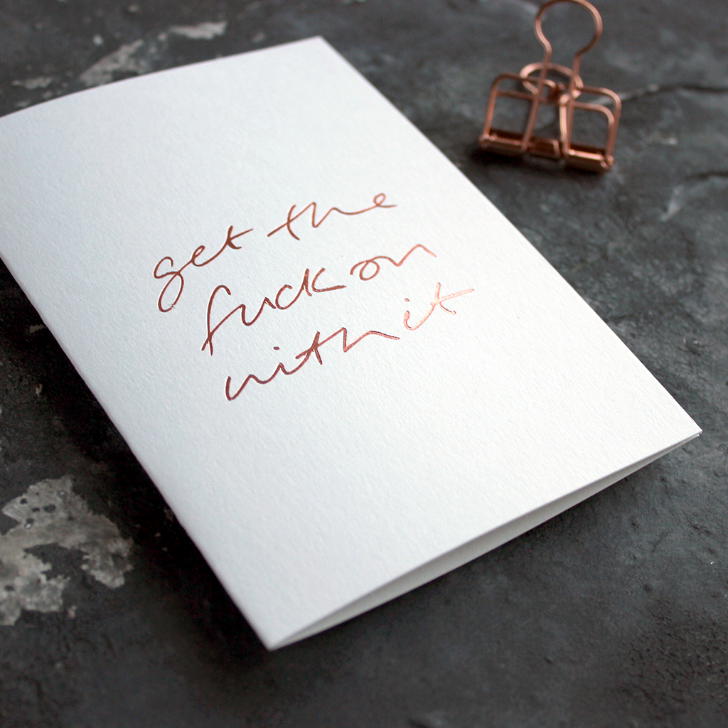 A white luxury card with the words 'Get The Fuck On With It' handfoiled in rose gold