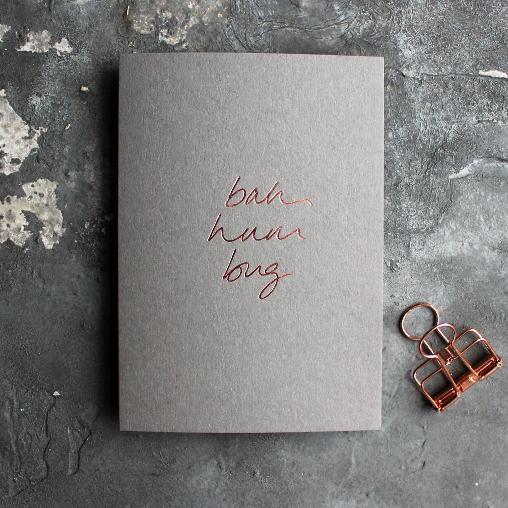 This grey christmas card has 'Bah Hum Bug' handprinted in rose gold foil in handwriting on the front.
