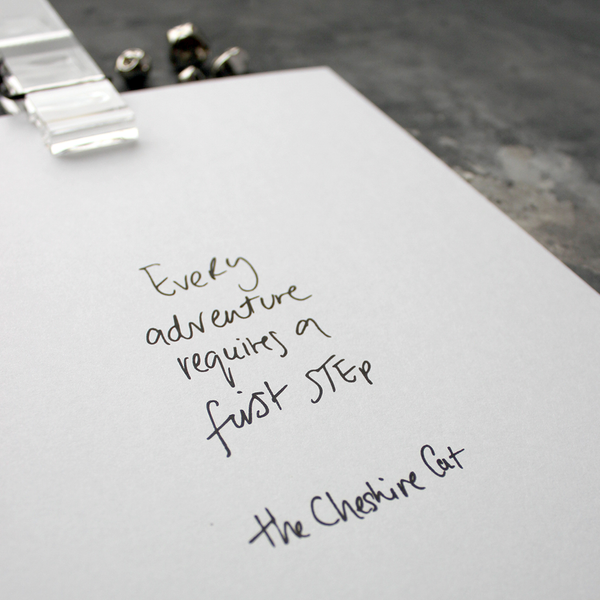 This handwritten children's cheshire cat print says 'Every Adventure Requires A First Step' in black on white paper.