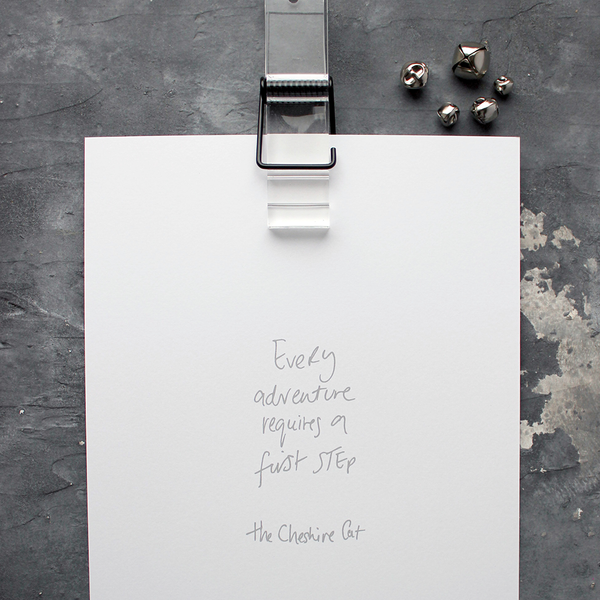 This handwritten children's cheshire cat print says 'Every Adventure Requires A First Step' in grey on white paper.