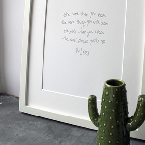 This handwritten children's Dr Seuss print says 'The more that you read, the more things you will know. The more that you learn, the more places you'll go' in grey on white paper.