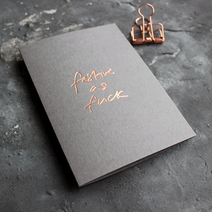 This grey christmas card has 'Festive As Fuck' handprinted in rose gold foil in handwriting on the front.