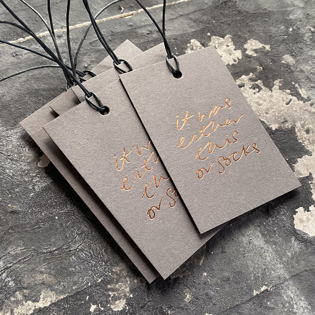 "Luxury grey gift tags with waxed cotton thread have ""It Was Either This Or Socks' handprinted in handwritten rose gold foil."