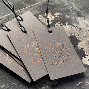"Luxury grey gift tags with waxed cotton thread have ""It's The Thought That Counts' handprinted in handwritten rose gold foil."