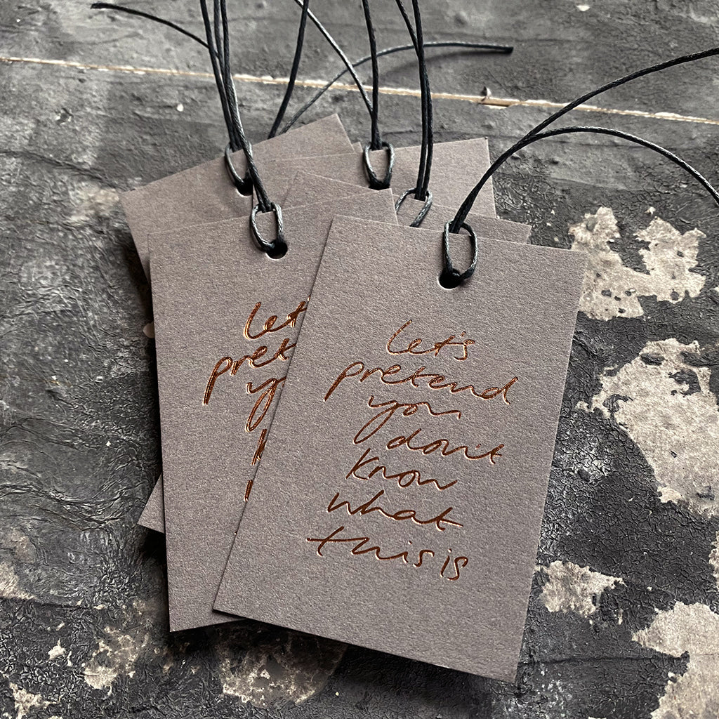 "Luxury grey gift tags with waxed cotton thread have ""Let's Pretend You Don't Know What This Is' handprinted in handwritten rose gold foil."