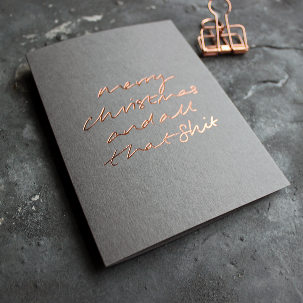 This luxury grey card has a hand foiled rose gold message on the front that says Merry Christmas and all that Shit