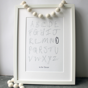 This children's personalised alphabet print is a unique hand drawn typography design in grey and black letters on white paper.