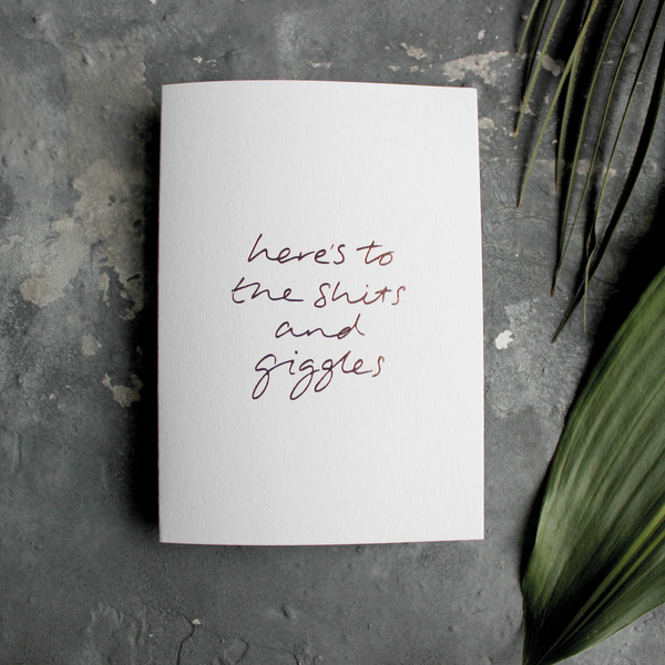 The front of the card has the phrase 'here's to the shits and giggles' handwritten and hand pressed in rose gold foil