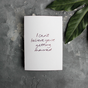 The front of the card has the phrase 'I can't believe you're getting married' handwritten and hand pressed in rose gold foil