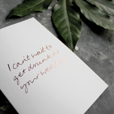 The front of the card has the phrase 'I can't wait to get drunk at your wedding' handwritten and hand pressed in rose gold foil
