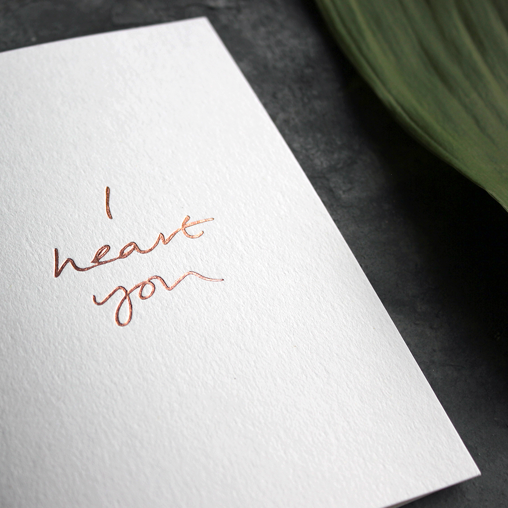 a luxury wedding card that is handwritten with a rose gold foil message saying I Heart You