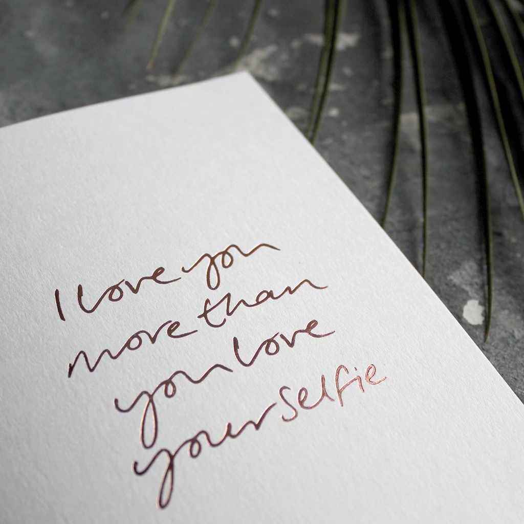 The front of the card says I love you more than you love your selfie and is stamped in rose gold foil