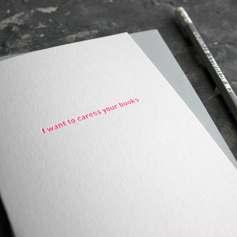 The front of the card says I Want To Caress Your Books hand pressed in neon pink foil