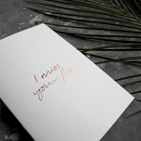 The front of the card says I Miss Your Face, handwritten and stamped in rose gold foil