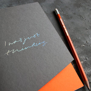 a grey and orange handmade luxury notebook that's hand foiled with the message I Was Just Thinking in holographic foil