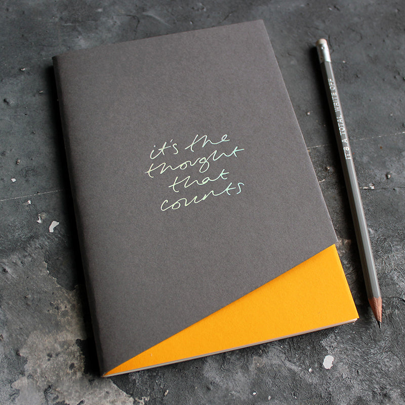 a grey and yellow coloured handmade luxury notebook that's hand foiled with the message It's The Thought That Counts in holographic foil