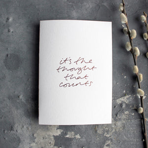 This rose gold hand foiled luxury white card says It's The Thought That Counts on the front in handwriting from Text From A Friend