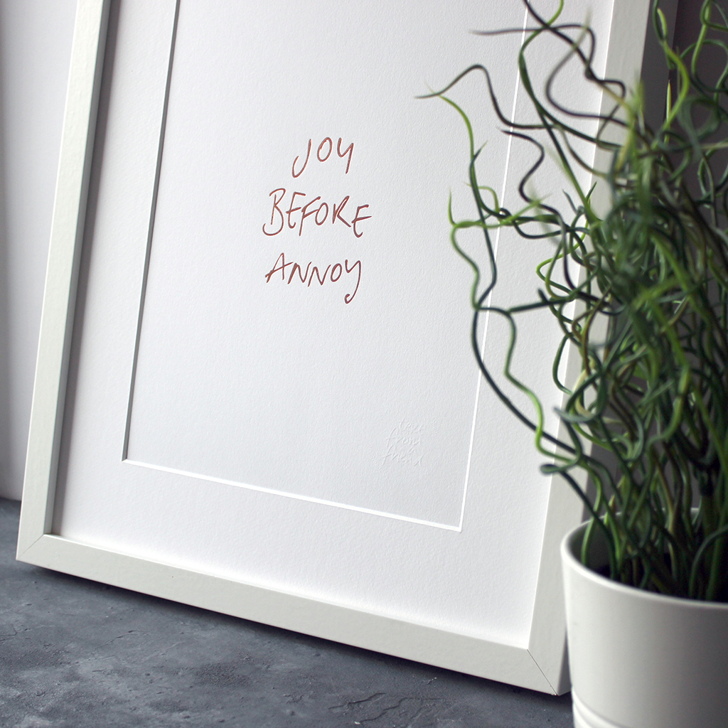 This unframed rose gold foil print has the words Joy before Annoy handwritten in a contemporary design