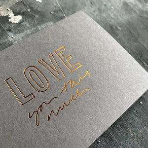 this hand foiled smoke grey coloured cash card says 'Love You This Much' on the front in bronze foil