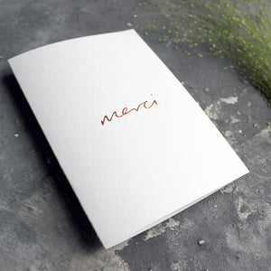 this white luxury card is hand foiled with the phrase Merci on the front