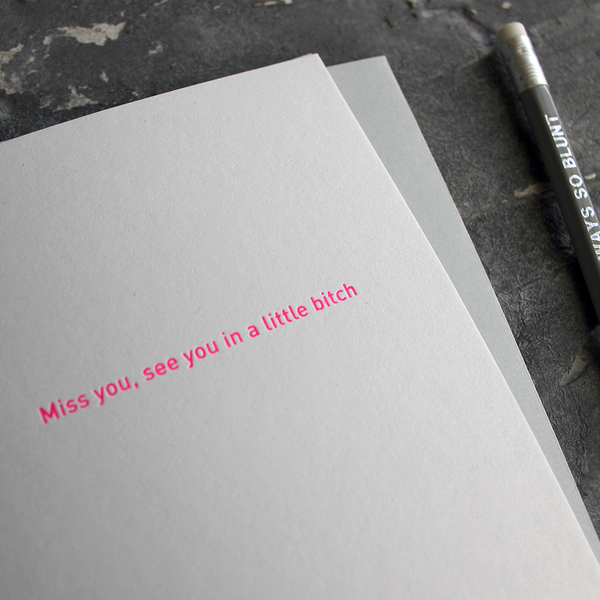 The front of the card says Miss You, See You In A Little Bitch and is stamped in neon pink foil on a pale grey card