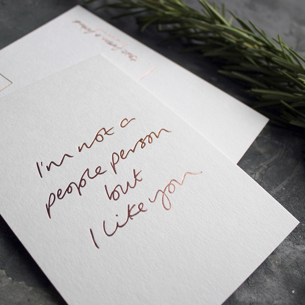 A luxury hand foiled postcard that says I'm Not A People Person But I Like You in rose gold foil