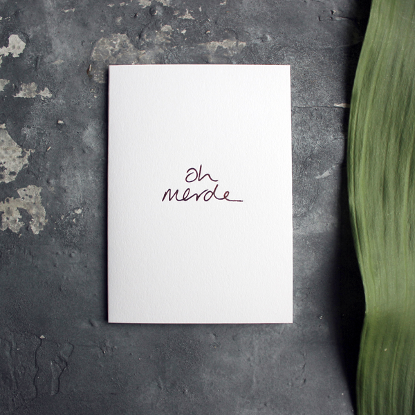 a luxury handwritten rose gold hand foiled message says Oh Merde on the front of the card