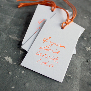 "Luxury white gift tags with waxed cotton thread have ""If You Don't Like It I Do' handprinted in handwritten orange neon foil."