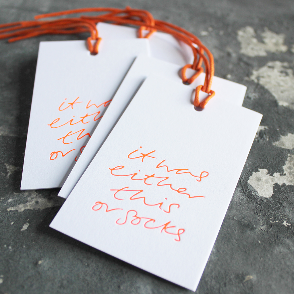 "Luxury white gift tags with waxed cotton thread have ""It Was Either This Or Socks' handprinted in handwritten orange neon foil."