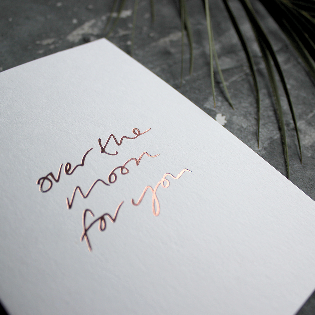 The front of this luxury card says Over The Moon For You and is handwritten and hand foiled in rose gold