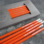 Orange HB pencils printed with silver foil phrases and packaged in a grey paper box.