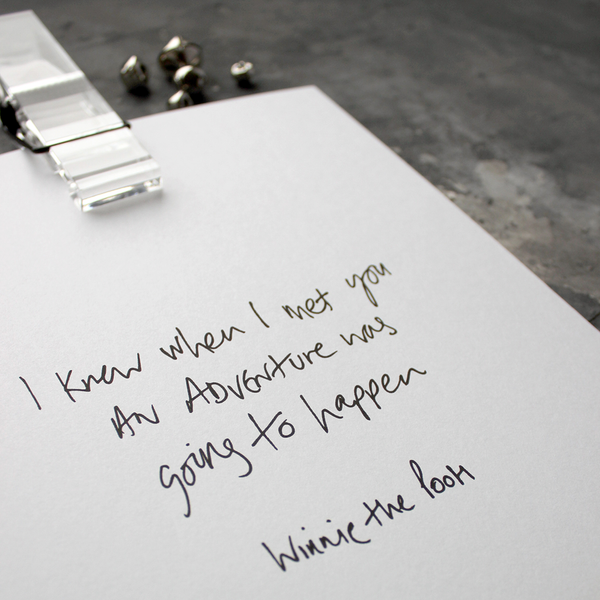 This handwritten children's Winnie The Pooh print says 'I Knew When I Met You An Adventure Was Going To Happen' in black on white paper.
