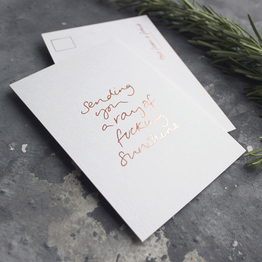 The Sending You A Ray Of Fucking Sunshine postcard is hand printed both sides in rose gold foil