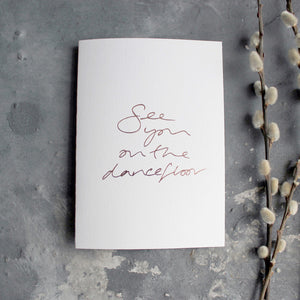 This luxury white hand foiled card says 'see you on the dancefloor' on the front