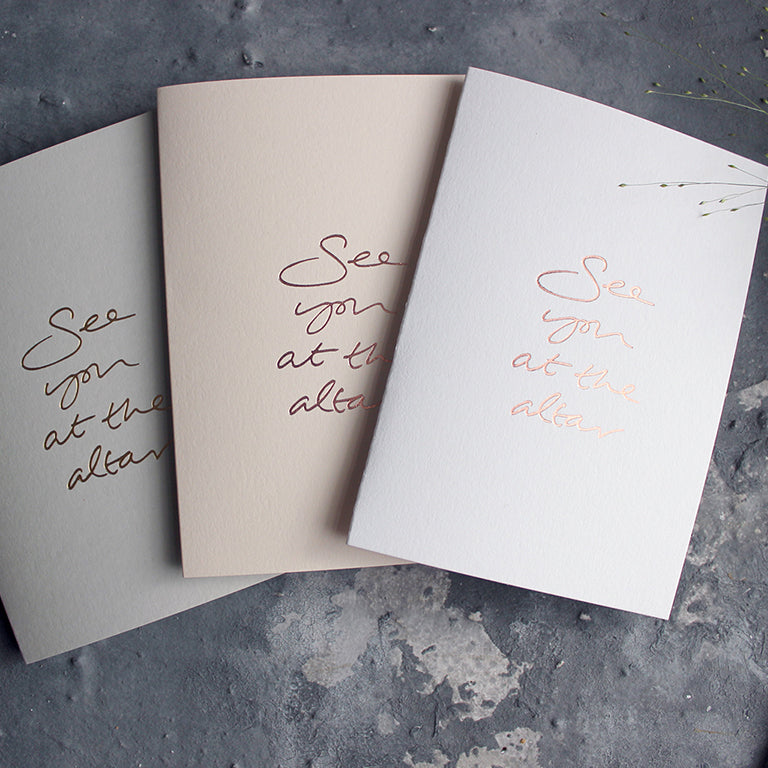 a luxury blush, white or pale grey wedding card that's handwritten with a rose gold foil message saying See You At The Altar