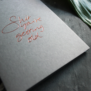 A luxury grey birthday card with the message 'Shit you're getting old' hand written and hand foiled in rose gold