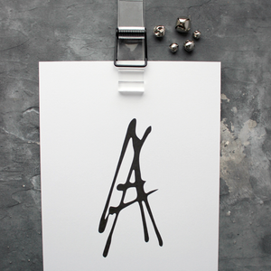 This initial print is a unique hand drawn typography design in black on white paper.