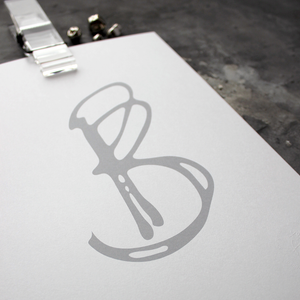 This initial print is a unique hand drawn typography design in grey on white paper.