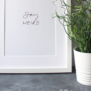 this unframed A4 print says Stay Weird and is handwritten and hand pressed in rose gold foil