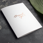 The front of the white luxury card says Thank You, handwritten and hand foiled in rose gold foil