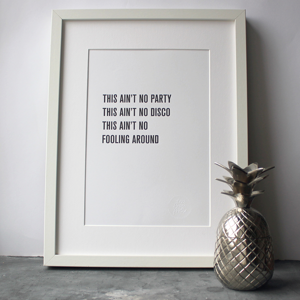 "The lyrics ""This Ain't No Party This Ain't No Disco"" from Talking Heads is a framed print in a typographic design"